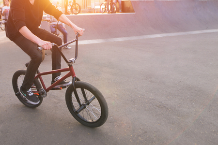 Bmx rider rides a skate park in the background of the sunset. Evening training at Bmx. Bmx Concept. Copyspace