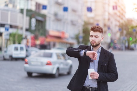 Portrait of a handsome business man standing with a cup of coffee in his hands, looking at the wrist watch against the background of a blurred urban landscape. Busy businessman looks at the clock.