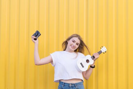 Cute, happy young model posing with white ukulele and retro camera on background of yellow wall.