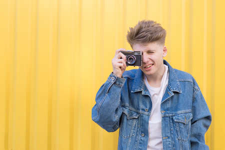 Hipster in a jeans jacket is on a yellow background and photographs on a retro film camera. Photographer on a yellow background.