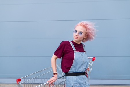 Fashionable girl with colored hair and eyeglasses poses with an apex and looks at the camera on the background of a blue wall. Stylish young girl with shopping carts. on a blue background.