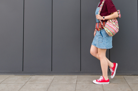 Girl's legs in red sneakers, backpack and denim dresses go down the ground against the background of a dark wall. Street portrait of girl's feet walking around the wall. Girl hipster on a walk.