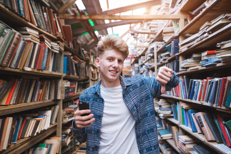 Handsome young man stands in a library with a smearphone in his hand and shows his finger down. The student does not like the library. Young people do not like books and libraries. Stok Fotoğraf