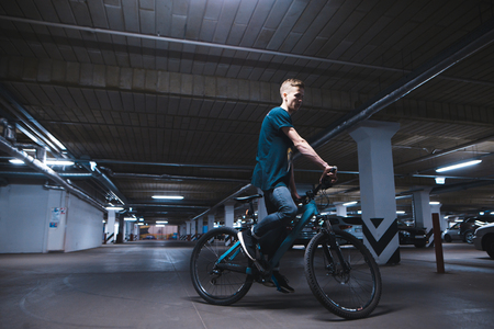 Portrait of a cyclist in an underground parking lot for cars. A man rides a bicycle by parking.
