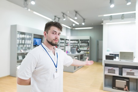 Consultant stands in the bright modern electronics store and invites you with a hand. Portrait of a consultant on the background of a light technology store.