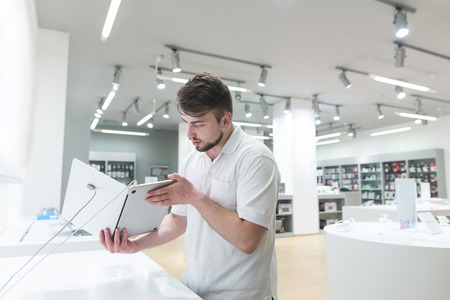 Handsome man looks at a notebook in a light tech store. A buyer chooses a notebook in a modern electronics store. Purchase a gadget. Stock Photo