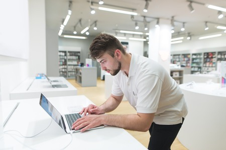 Handsome man uses a notebook in a modern technology store with a stylish interior. The buyer selects the notebook in the electronics store. Stock Photo
