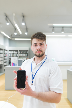 Portrait of a technology store consultant with a smartphone in his hands. The husband's consul is in the electronics store with a smartphone in his hands.