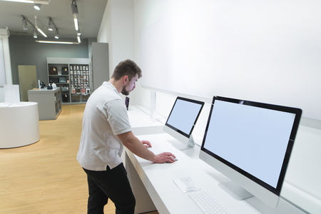 Buyer uses a monoblock computer in a modern technology store. A man with a beard chooses a computer at an electronics store. Purchase of a modern computer.