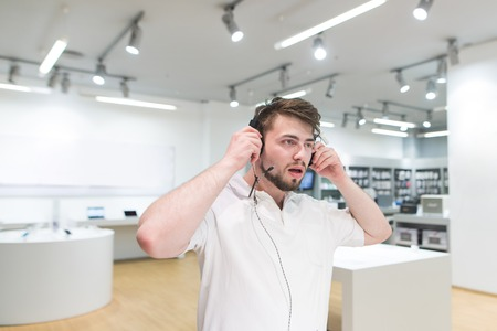 Portrait of a buyer who listens to music in headphones on the back of a tech store. A man in a white T-shirt and a beard selects headphones in the electronics store. Buying headphones. Stock Photo