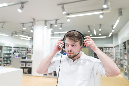 Handsome man in a white T-shirt stands in a technology store and wears headphones on his head. Choosing and buying headphones in the electronics store. Stock Photo