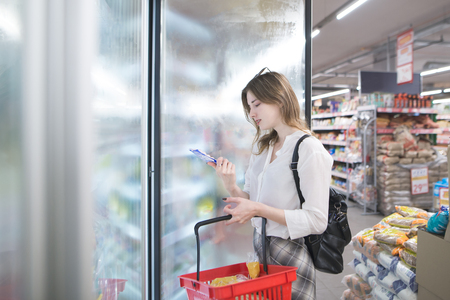 Attractive young woman stands at the refrigerator in the store with frozen food in his hands. Young girl with a red basket buys frozen food at a supermarket. Фото со стока