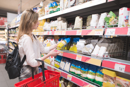 Woman with a red shopping basket and a package in her hands is in the supermarket on the background of shelves with the products. Girl buys groats the grocery store. Shopping in a supermarket. Stok Fotoğraf