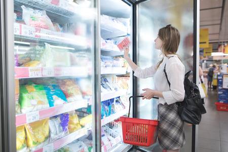 Stijlvolle vrouw koopt diepvriesproducten in een supermarkt. Aantrekkelijke jonge vrouw staat naast een vriezer en kiest diepvriesproducten. Aankoop van producten in een supermarkt.