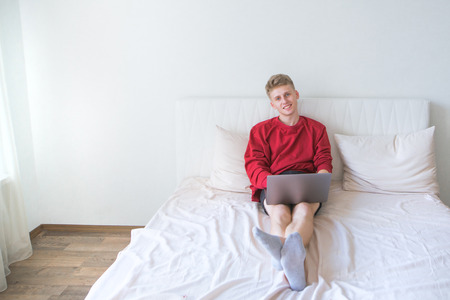 Smiling young man in a red sweatshirt sits on the bed in a bright room and works on a laptop and looks at the camera. Work at home on the internet concept. Freelance Stock Photo