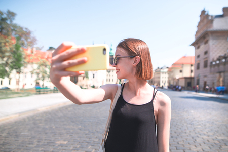 Attractive tourist girl in a black dress takes selfie against the background of the old city. Walking along the old city on a sunny summer day.Happy woman tourist taking selfie street of the old city