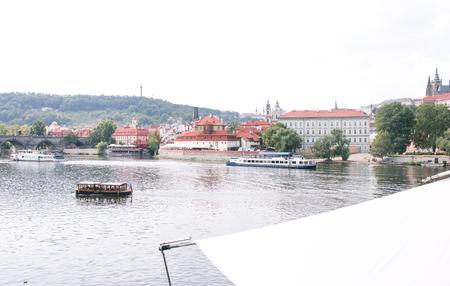 Landscape of Prague on the summer sunny day, the river Vltava. Ships float along the Vltava in Prague