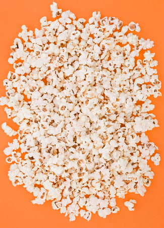 Background. Popcorn on a bright orange background, top view. Flat lay. Copyspace. Cinema Concept.