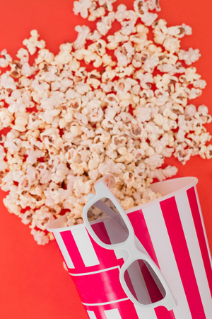 Popcorn in a paper bowl and 3d glasses for watching a film on a red background, top view. Flat lay. Copyspace. Cinema Concept. Stock Photo