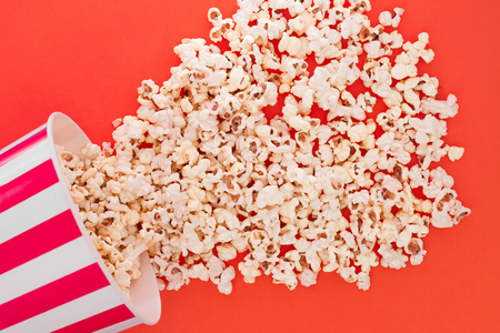 Popcorn rises from a paper bowl to a red background, a view from above. Cup with popcorn is isolated on a red background. Flat lay. Copyspace. Cinema Concept.
