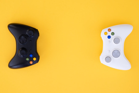 Black and white joystick on a yellow background. White and black gamepad is isolated on a yellow background. Video game competition. Gaming concept. Top view. Flat lay