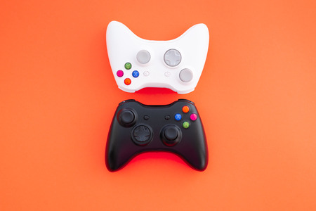 Two joysticks, black and white on a red background. The white and black gamepad are isolated on a yellow background. Gaming competition. Gamer concept. Videogame control confrontation concept. Banque d'images - 109512703