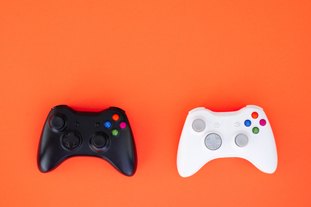 Two joysticks, black and white on a red background. The white and black gamepad are isolated on a red background. Gaming competition. Gamer concept. Videogame control confrontation concept. Copyspace Banque d'images - 109512717