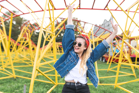 Happy smiling girl in stylish clothes and sunglasses rejoices with her hands raised in the background of slides in an amusement park. Rest in an amusement park.