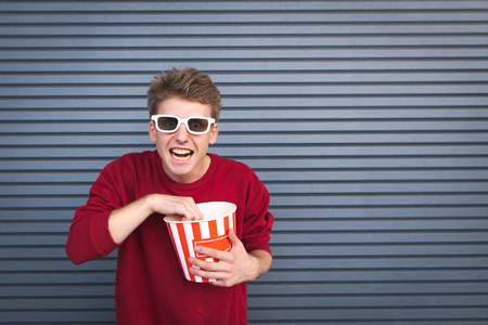 Crazy young man in 3D glasses eating popcorn cup and looking at the camera against a dark background. Emotional man watches a movie. Cinema Concept. Copyspace