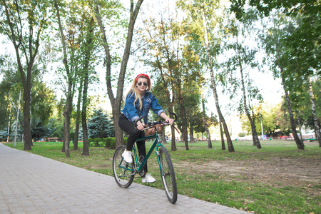 Young girl in stylish clothes and sunglasses rides a green bike in the park. Walk on the bike. Active leisure concept