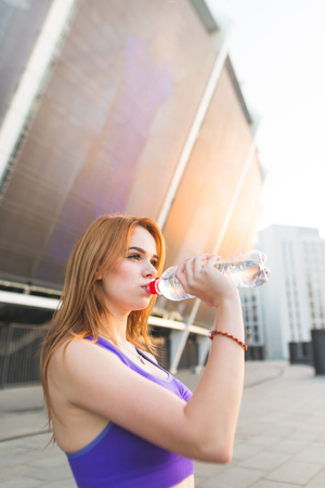 Sporty young girl wearing sportswear drinking water from a bottle on the background of a modern building and sunset, looking sideways. Sports concept. Athlete quenches thirst with water.