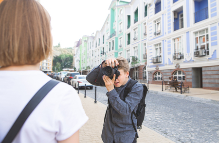 Backstage. Photographer photographs a girl on the streets of the town. Model poses, photographer picks up. Outdoor photosession. Photographer works with a model on the street
