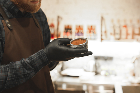 Close up photo of male barista with a beard holding a portafilter and preparing coffee in his coffee shop. Bartender holds a holder with grinded coffee. 免版税图像