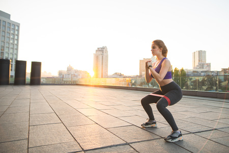 Portrait of a charming girl in sportswear doing training in the background of the sunset. Girl squats with a rubber band on the street. Sport in the morning.