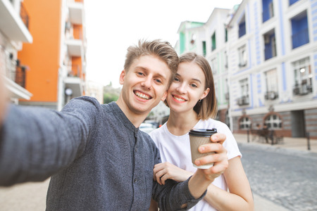 Smiling young man with a cup of coffee in hand takes selfie with his girlfriend in the background street of the town. Beautiful young couple makes selfie and smiles.