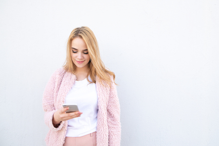 Pretty girl in a pink coat and white T-shirt uses a smartphone and smiles on a white background. Aattractive lady writes a message on the smartphone. Copyspace Stockfoto