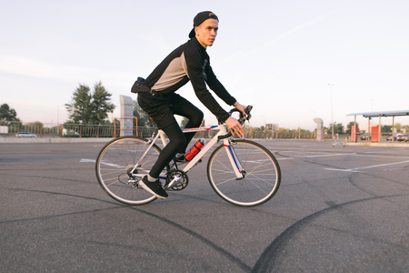 Young cyclist rides in a car parking lot for a bike. Rider wears a bike in dark sportswear