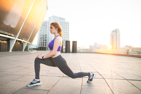 Sports girl doing stretching, warming up before training. Fitness girl in sports wear stretches on training. Morning sports on the background of the city in the east sun.Woman and Sports.