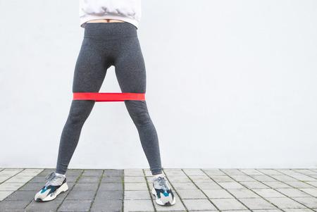 Chica con hermosas piernas musculosas se pone en cuclillas con una banda elástica roja sobre un fondo blanco, piernas de primer plano y un lugar para el texto. Copyspace. Concepto deportivo.