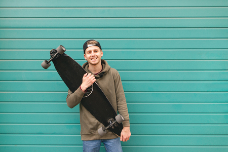 Happy skater in casual clothing stands with a longboard in his hand against the background of a turquoise bright wall, looks at the camera and smiles. Copyspace