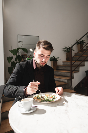 Portrait of a business man sitting in a cozy restaurant and dining with salad and coffee. Man in a business suit eats in a light restaurant.