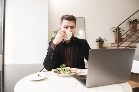 Business man drinks coffee and uses laptop in a cafe. Busy man sits in a cozy restaurant with a cup of coffee in his hands, a plate of food on the table and looks at the laptop screen. Banco de Imagens