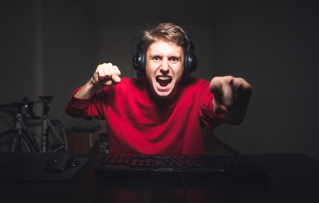 Young man playing game at home and streaming playthrough or walkthrough video. He is going to make revenge that's why he is holding his fists in attack position