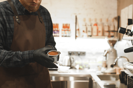 Bearded barista is holding a portafilter with coffee and ready for preparing espresso at the coffee shop. Close up photo of bartender with a holder with grinded coffee at the cafe.