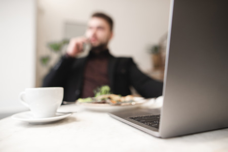 Blurred background. Business man works on a laptop, eats and drinks coffee. Work in a cafe. Freelance Concept. Focus on the notebook keyboard.