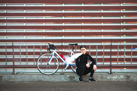 Cyclist sitting by a bike, smoking a vape on the background of the wall and looking at the camera. Young man with a bike smoke e-liquid instead of nicotine cigarettes. Copyspace