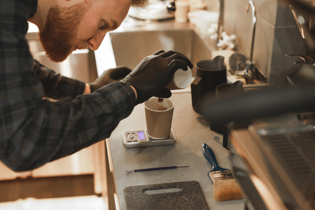 Concentrated barista with a beard is pouring coffee to the paper cup and weighing it on the kitchen scales. Focused bartender weighs coffee on the electronic scales at coffee shop. Close up photo.