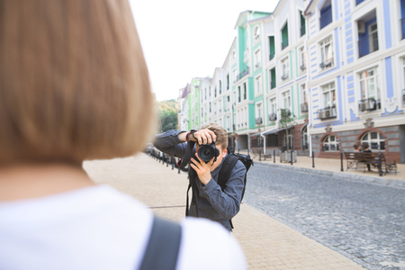 Photographer photographed model on the street of the town. Portrait of the photographer at work. Photosession concept Imagens