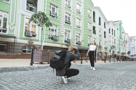 Backstage. Work of the photographer and model on the streets of the town. Professional photographer with a backpack photographs a young attractive girl on the streets of the town. Photosession concept
