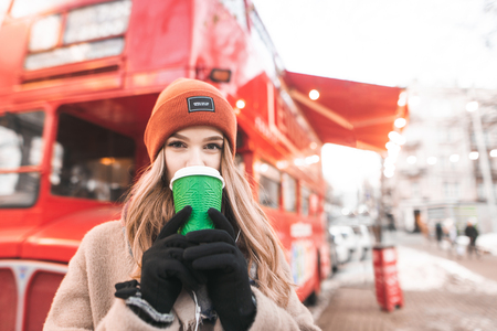 Portrait of a cute girl on warm clothes, standing on the background of a red bus cafe, drinking coffee from a cup, looking camera. Beautiful student girl drinking coffee at a walk on a spring cold day Stock Photo
